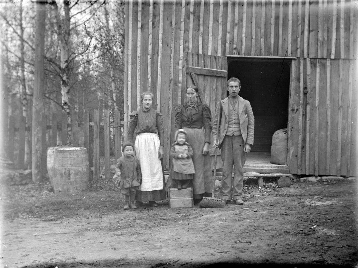 Tre voksne og to barn foran ukjent uthusbygning, antagelig i Follebu eller Østre Gausdal