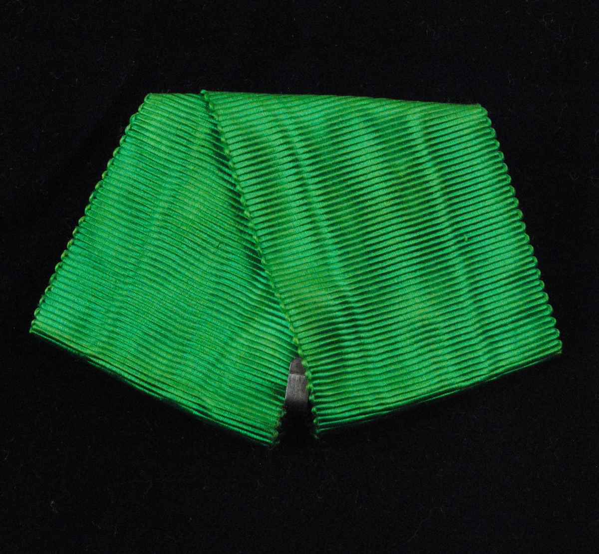 Ett grönt ordensband av siden som har tillhört en Vasaorden, ett riddarkors. Bandet har ett par metallkrokar fastsydda på baksidan för att kunna fästa orden vid klädseln. Själva ordenstecknet saknas då en Vasaorden efter mottagarens död måste återlämnas.