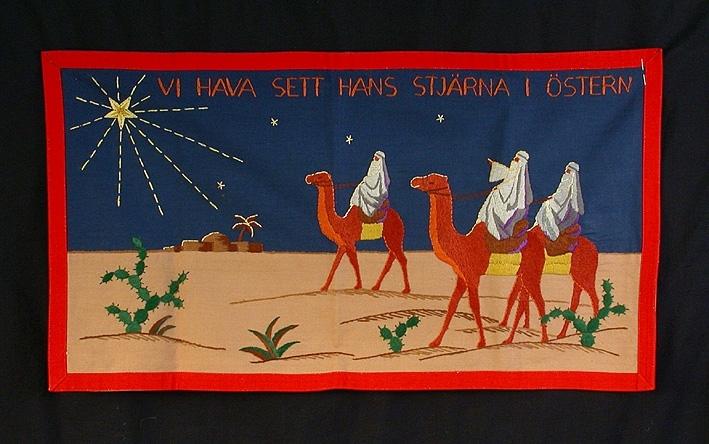 Broderad bonad i bottentyg av blått och beige bomullstyg. Föreställer de tre vise männen ridande i öknen på kameler mot betlehemstjärnan som lyser med långa strålar. Broderat med yllegarn i plattsöm i färgerna gult, brunt, grått, grönt och lila i blandade nyanser. Sydd ram i rött 2 cm brett bomullsband. I överkanten broderad text: VI HAVA SETT HANS STJÄRNA I ÖSTERN.