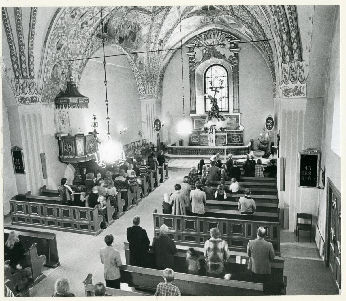 Dingtuna sn, kyrkan.  Gudstjänst i Dingtuna kyrka. Åhörarna står i kyrkbänkarna och prästen står vid altaret.