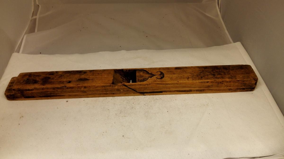 1 langhövel.  Langhövelstok av gammel type med hulkil langs siderne. Tand mangler.  Kjöpt paa auktion efter Peder Rudsvik, Kaupanger.