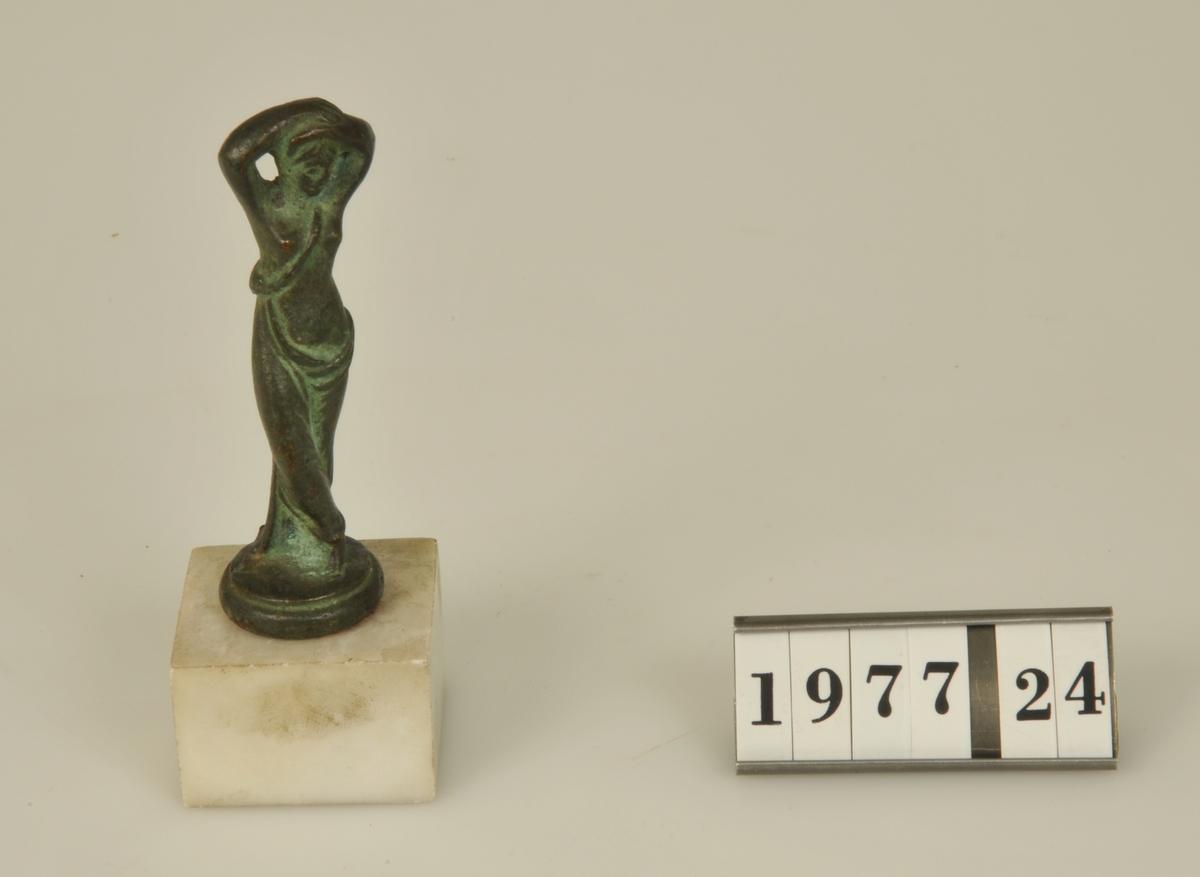 Kvinnofigur. Monterad på marmorplatta.  Höjd: Totalt 10,2 cm.          Statyetten 7,7 cm.