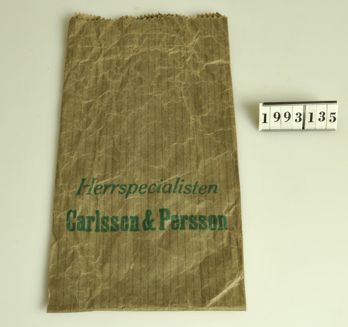 """Grön text:""""Herrspecialisten Carlsson & Persson""""."""