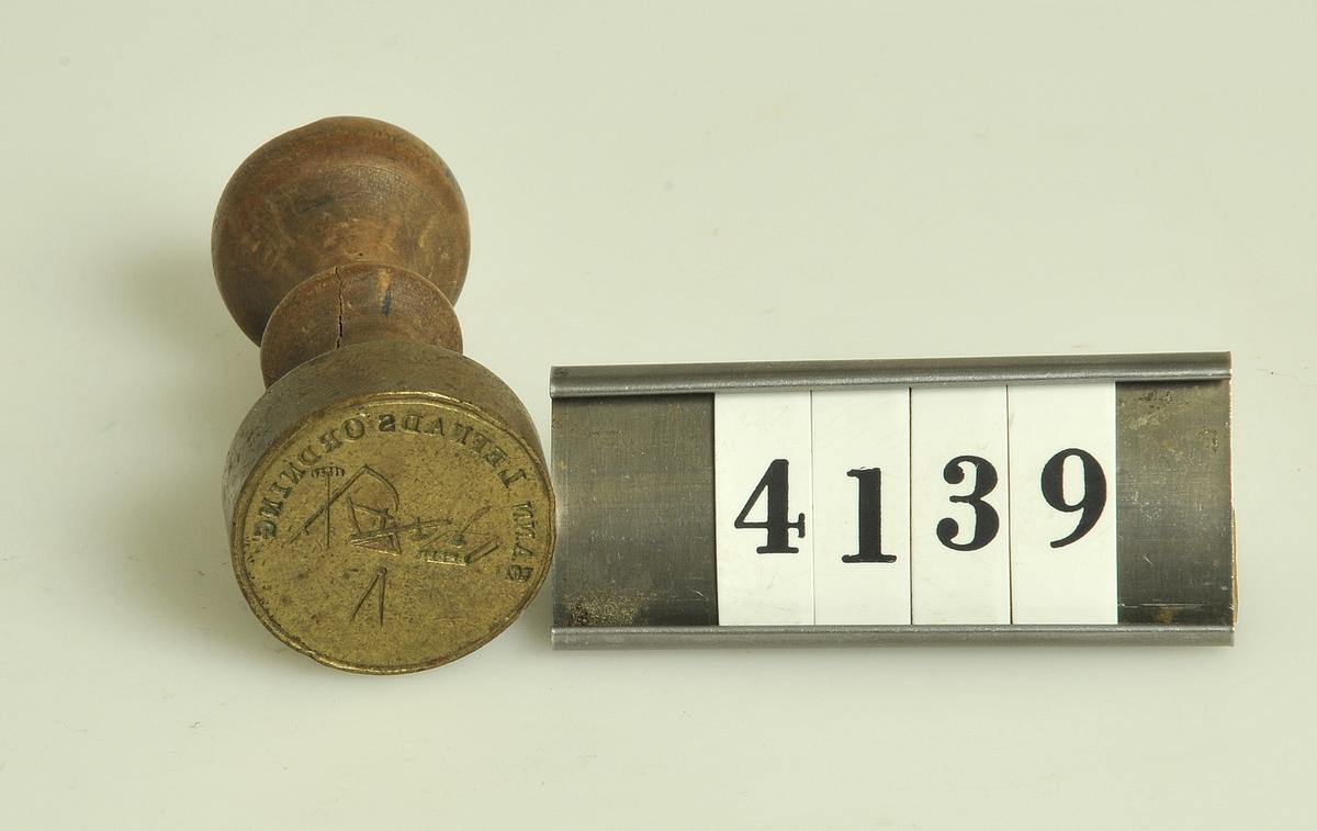 """Rund form. Av mässing med svarvat träskaft. Motiv: Räfsa, lie, plog, bok och penna, omgivet av texten """"Sann lefnads ordning""""."""
