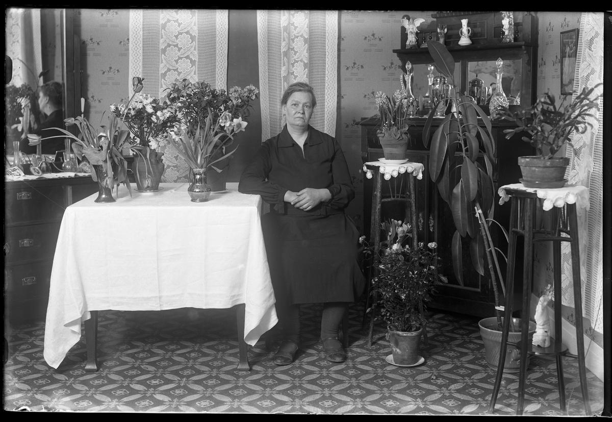 """En kvinna sitter vid ett bord, omgiven av blommor. Fotografiet taget i samband med hennes 50årsdag. I fotografens anteckningar står det """"Fr. Johansson 50år""""."""