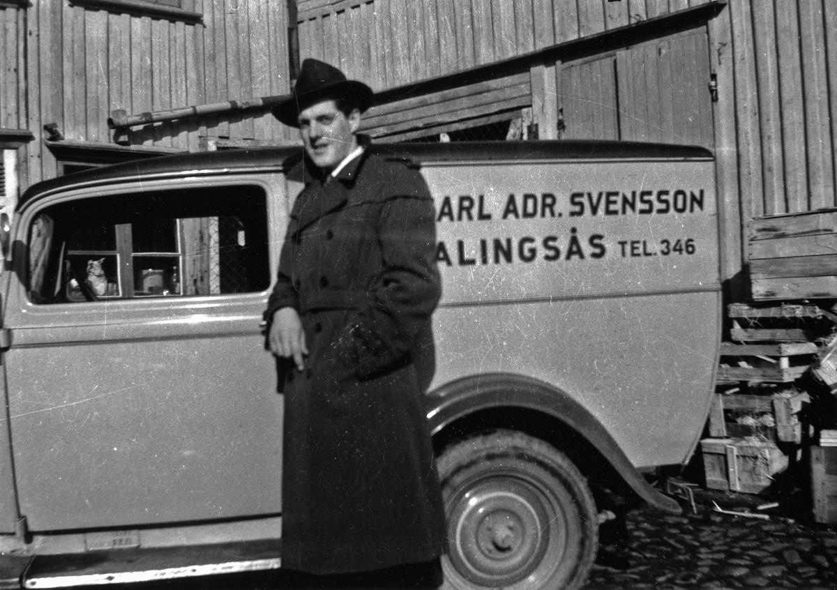 Fotograf Gunnar Persson, iklädd hatt och trenchoat, vid varubilen till Firma Carl Adrian Svensson. Gunnar Persson var en tid anställd vid firman som var en partiaffär i mjöl, socker, fodervaror, bensin och oljor.