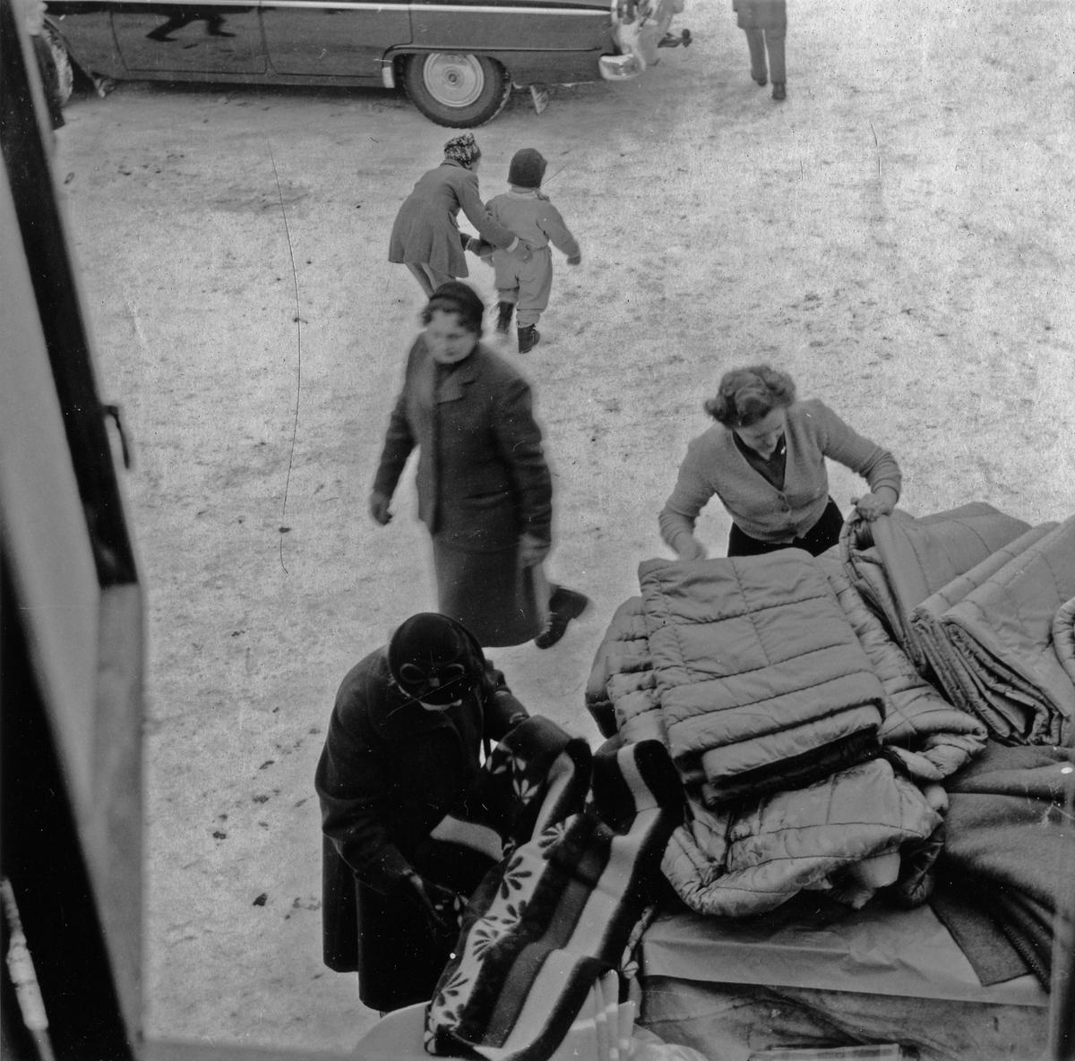 Vy från fönster uppifrån, tittar ned mot ett 3 kvinnor som inspekterar filtar och madrasser på auktion på gården till Tells hus. En bil syns i bakgrunden. Kvarteret Jägaren 11. Kungsgatan 38.