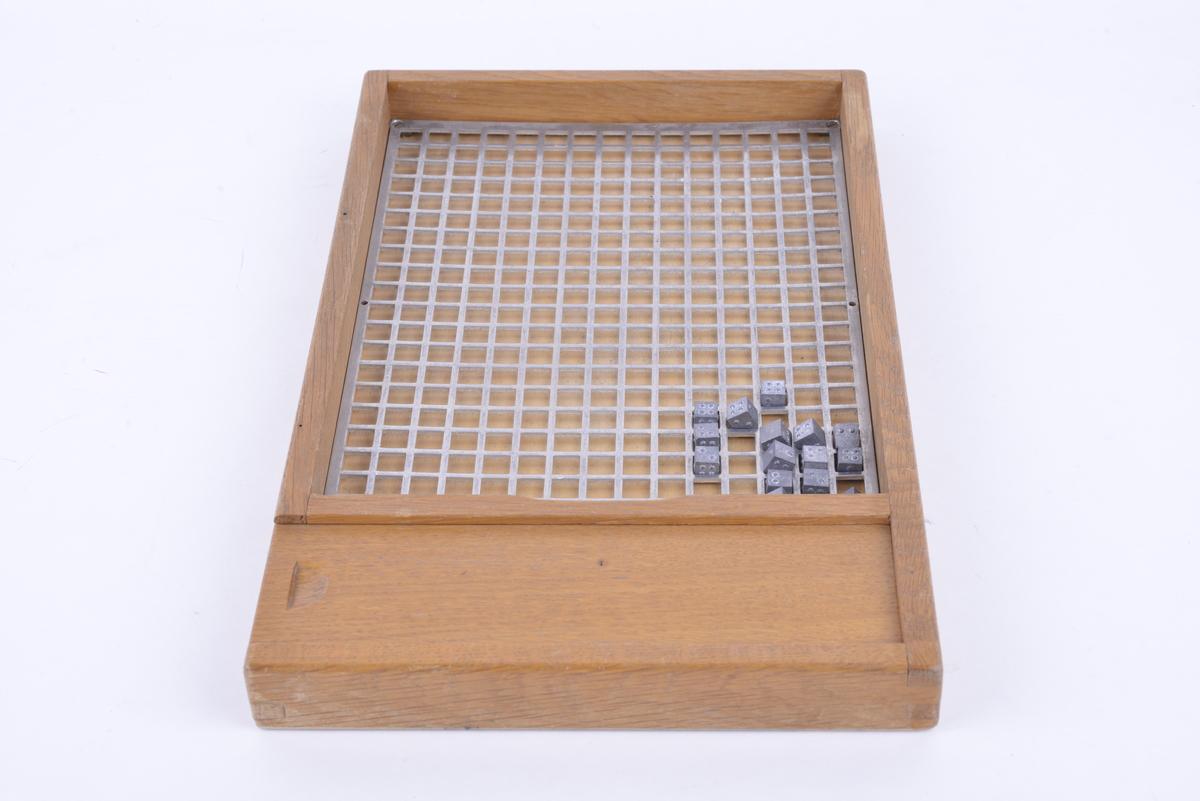 Rektangulært brett av tre. Bunnen har en metallplate med kvadratiske hull i. 132 kvadratiske metallterninger med punkt-tegn på, som kan plasseres i metallplaten. Brettet har en skuff på den ene kortsiden, der brikkene kan oppbevares.