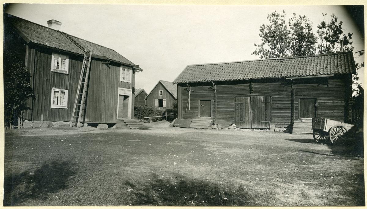 Gunnilbo sn, Gunnilbo by.  Gårdsbild med bostad, uthys, kärra m.m. Stege står lutatd mot huset.