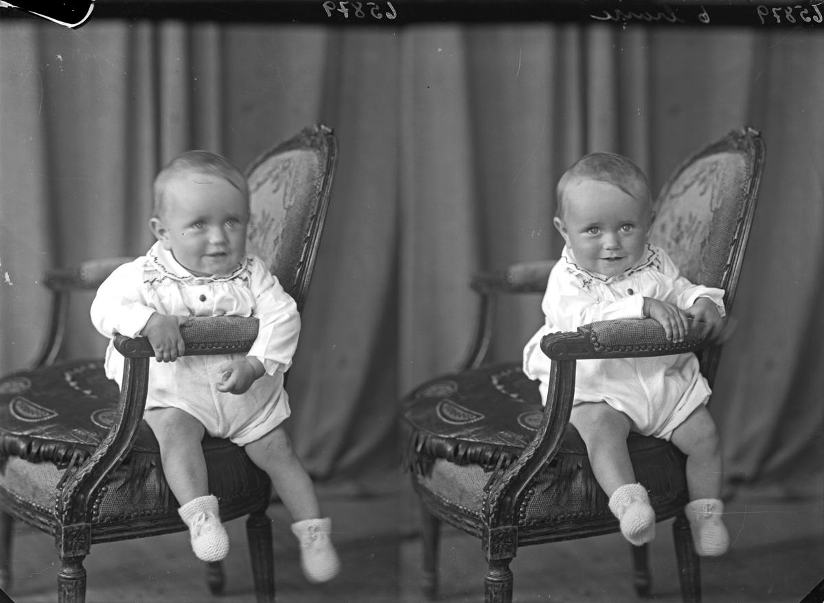 Portrett. Liten gutt i lys drakt sittende på tvers i en brodert stol. Bestilt av Fru Olly Haugsnes. Rossebøe.