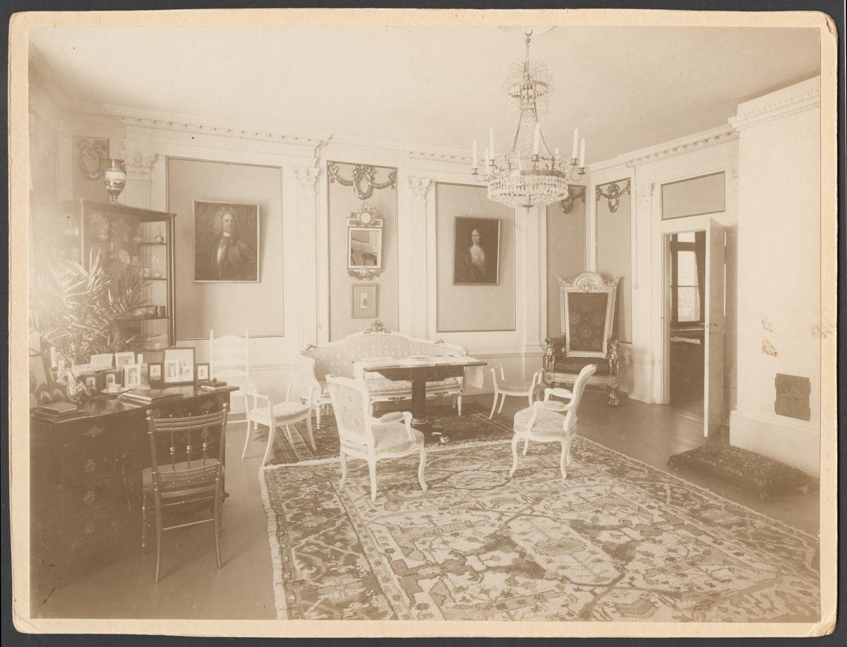 Bilden visar salongen (rum 114) i varvschefsbostället åren 1908-1912. Rummet är inred med klassicistisk interiör. Golvet är täckt med en stor matta och möblerna har arrangerats längs väggarna. Dörren står öppen och leder blicken vidare till salogen (rum 113).