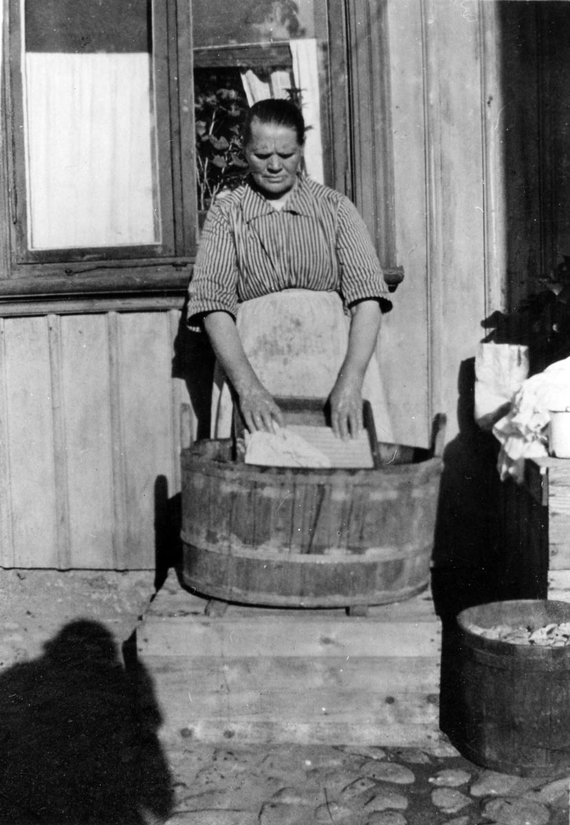 Amanda Dahlgren skrubbar tvätt i en tvättbalja på gården, Solgatan 7.