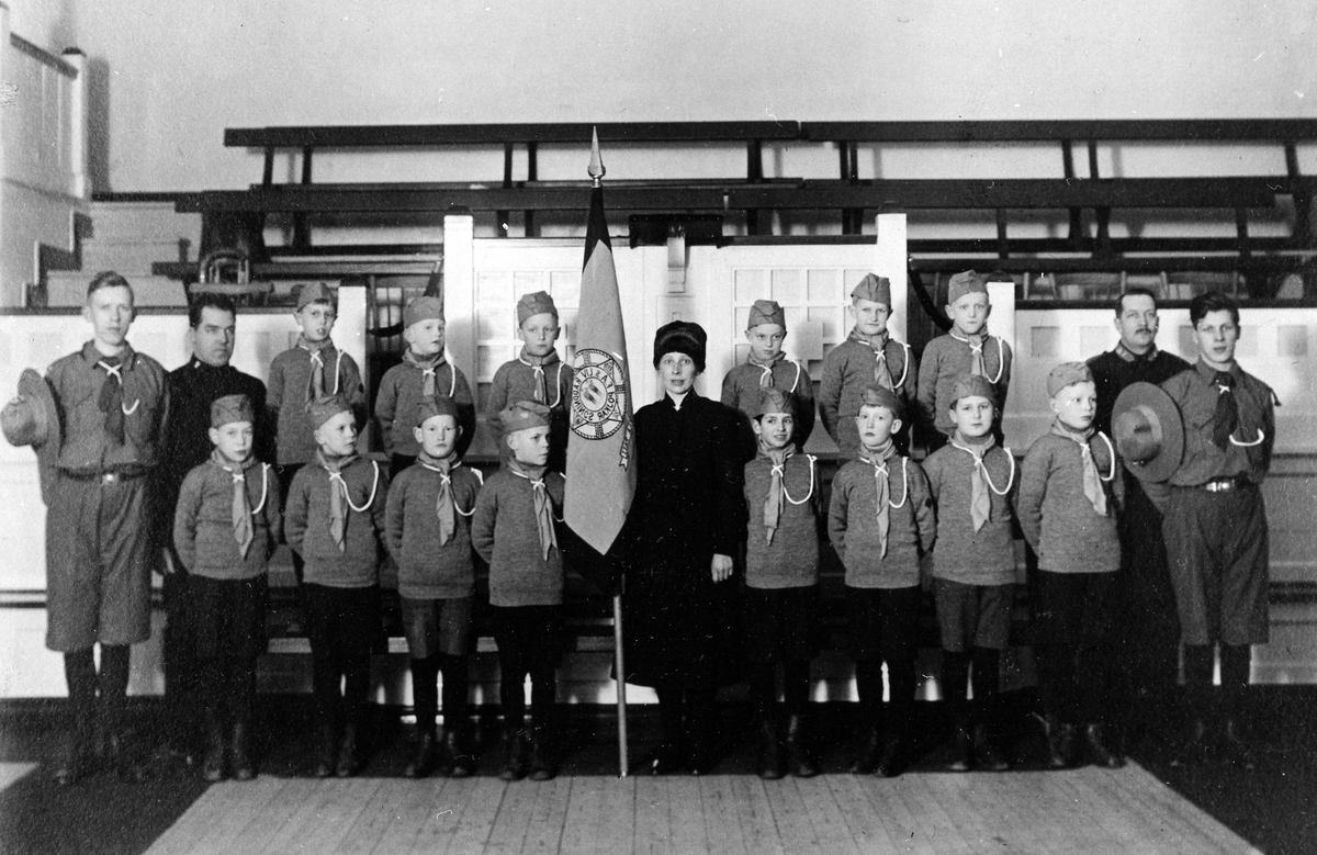 Gruppbild med 14 livräddningspojkar, 4 män, samt 1 kvinna (till höger om klubbflaggan). Alla 14 pojkar samt de två yngre männen står i uniform.
