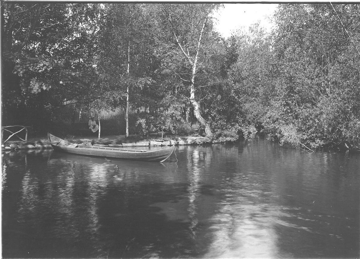 Offerholmen på Skansen. I dammen finns en roddbåt, på en bänk på stranden sitter en flicka.