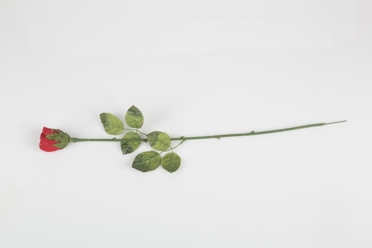 """Sløyfe med flaggets farger innsamlet etter terrorhandlingen 22. juli 2011 fra minnesmarkeringene i Lillestrøm.   Det er to roser. Rosen består av en grønn, ruglete plaststilk, blader og en rose som er i ferd med å springe ut.. Det er to bladgrener på stilken, med tre blader på hver gren. Rosen, som er rød, er ikke helt utsprunget men litt mer åpnet enn en knopp.  Det er planke """"perler"""" av lim som kanskje illuderer at rosen er duggfrisk på selve blomsten. Det kan også være at noen har sølt på rosen.  Det er torner av plast på stilkene."""