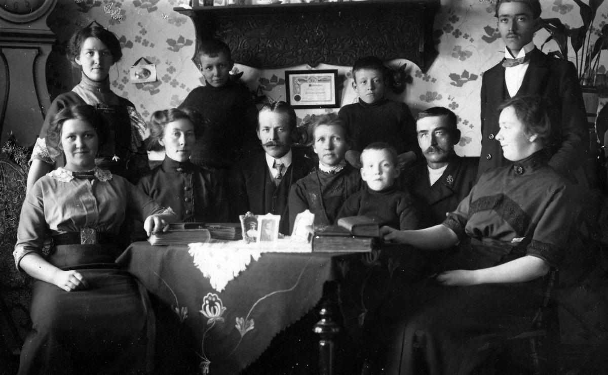 En familj samlad vid ett bord. Diplomet på väggen härrör från någon nykterhetsorganisation.