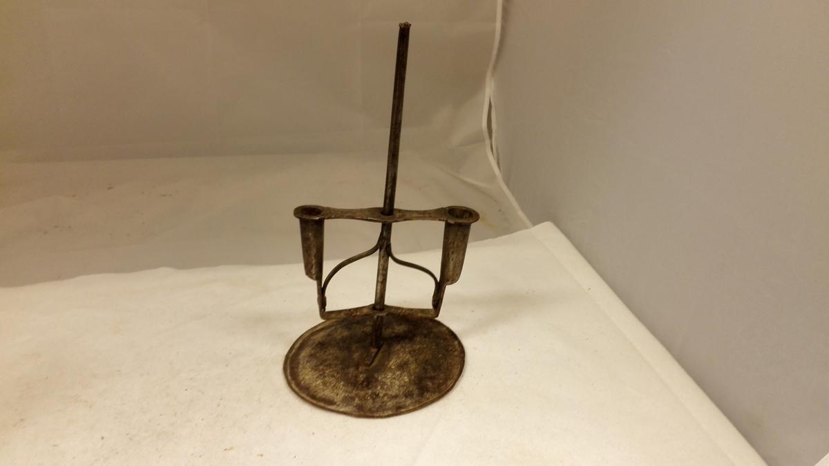To-armet lysestake av jern.  Fotplate med jernblik, rund med opadbøiet kant, diameter 15,8 cm. Til denne er klinket en 18 cm lang, rund jernstang, hvorpaa de to med hinanden forbundne lysehylster, der er dreibar og skyvbar paa stangen er anbragt. Gave fra stortingsmand S.T. Næss, Høiheimsvik.