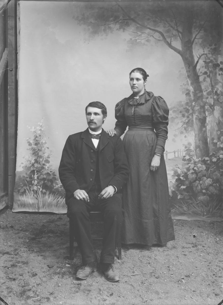Yngre par i mørk kjole og dress. Atelierfoto