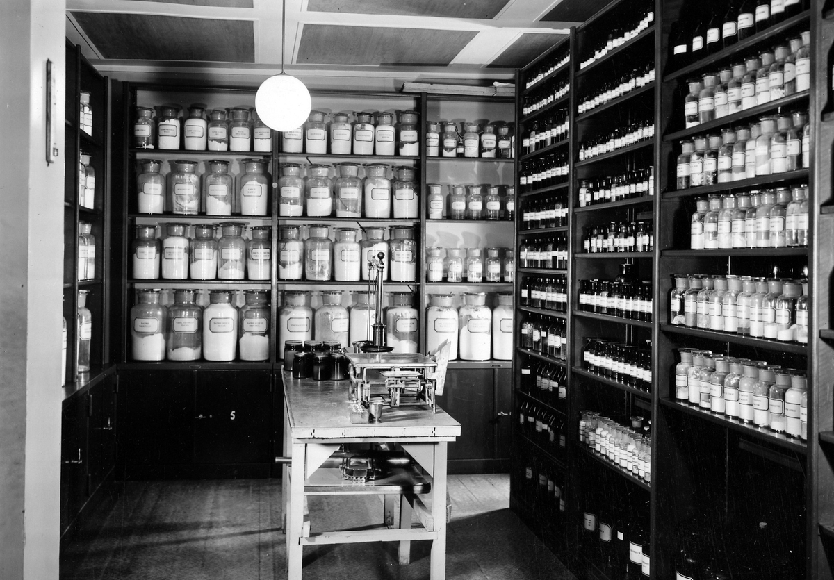Materialkammare på apoteket Hjorten. Bilden visar ett rum med hyllor från golv till tak med glasflaskor i alla dess storlekar. I mitten en liten arbetsyta.