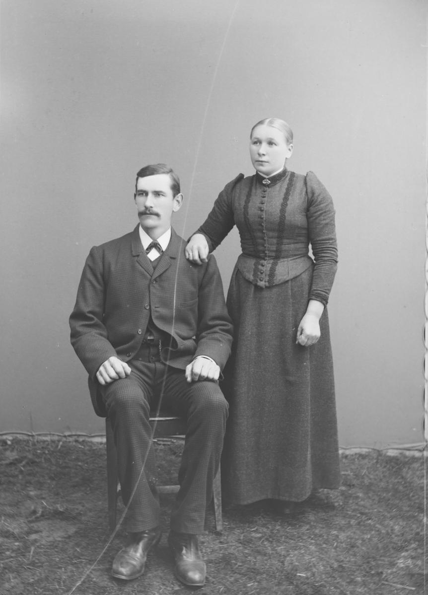 Yngre par med dame i drakt med puffermer og mann, sittende i mørk dress