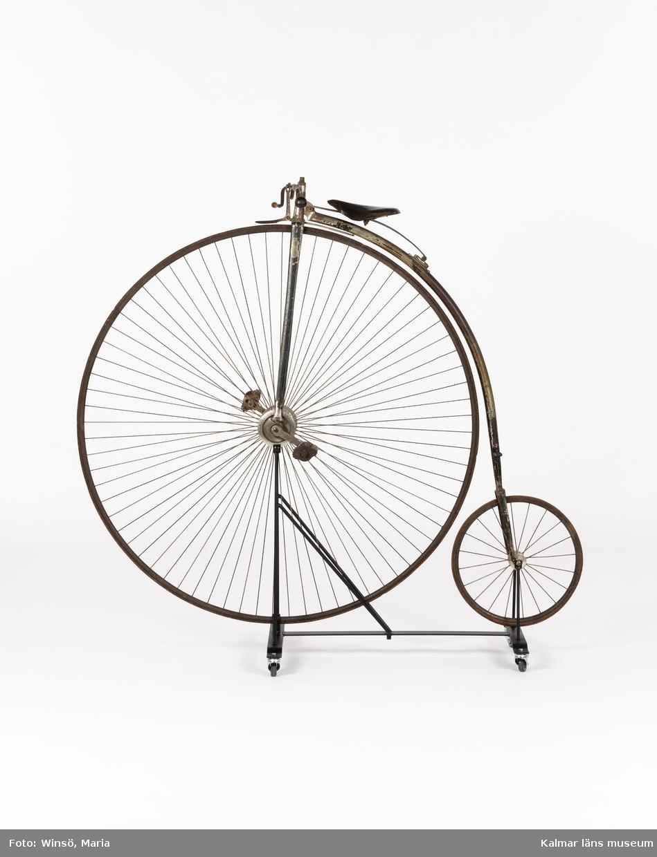 KLM 17889. Velociped. Höghjuling. Av metall med gummiklädda hjul. Velocipeden har handbroms samt ett fotstöd att använda när man ska ta sig upp på cykeln. Sadel av läder. Engelskt fabrikat, stämpel på bågen där sadeln är fastsatt: J. Devey & son, Special, Express, Wolverhampton.