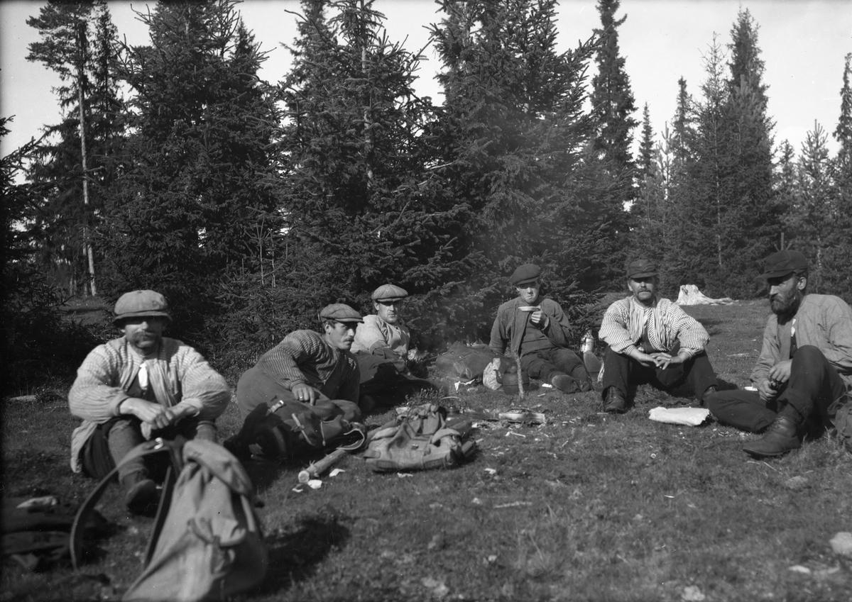 Seks menn slapper av i skogen (skogsarbeidere).