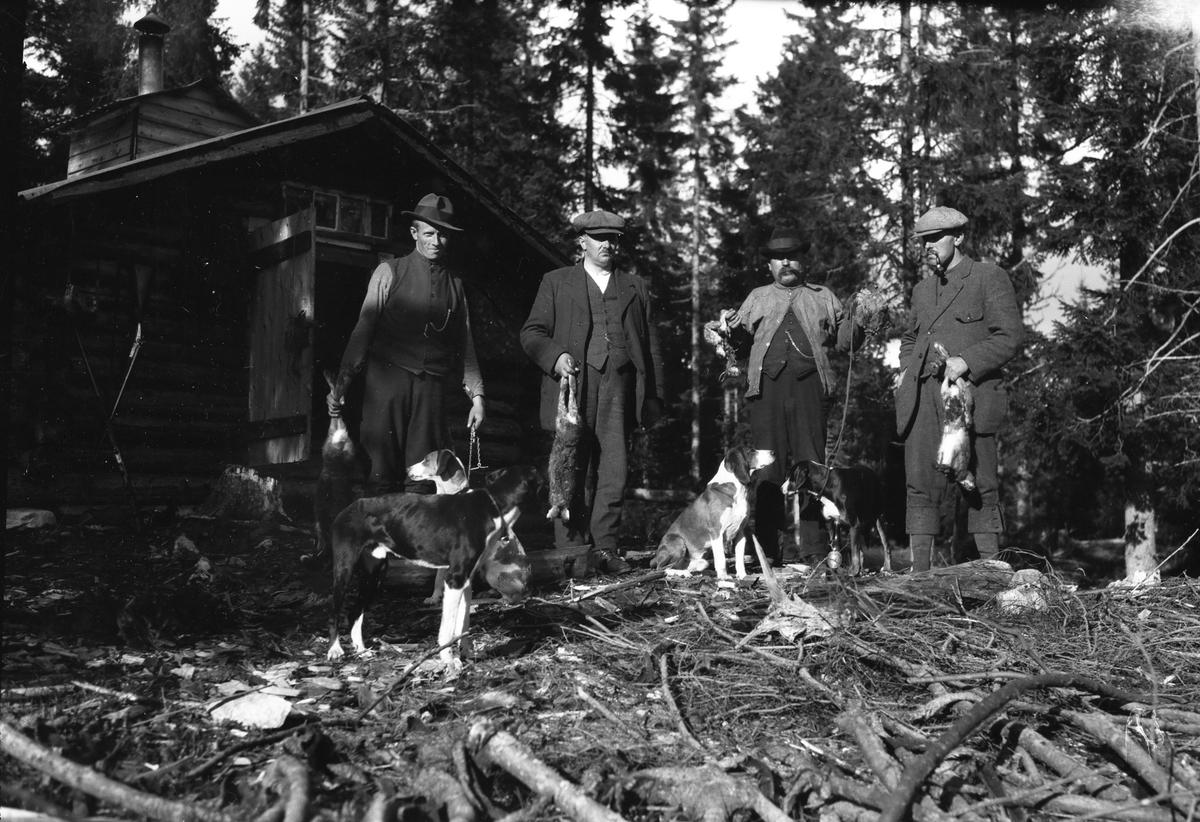 Jegere med hunder og jaktbytte i skogen.