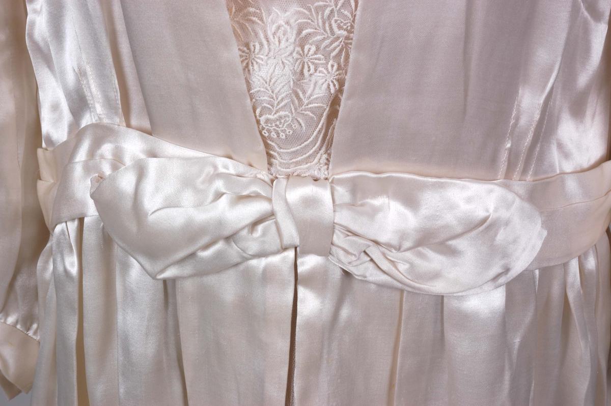 Knelang brudekjole i blank, benhvit silkesateng. Dekorert med innfellinger av tyllblonde.