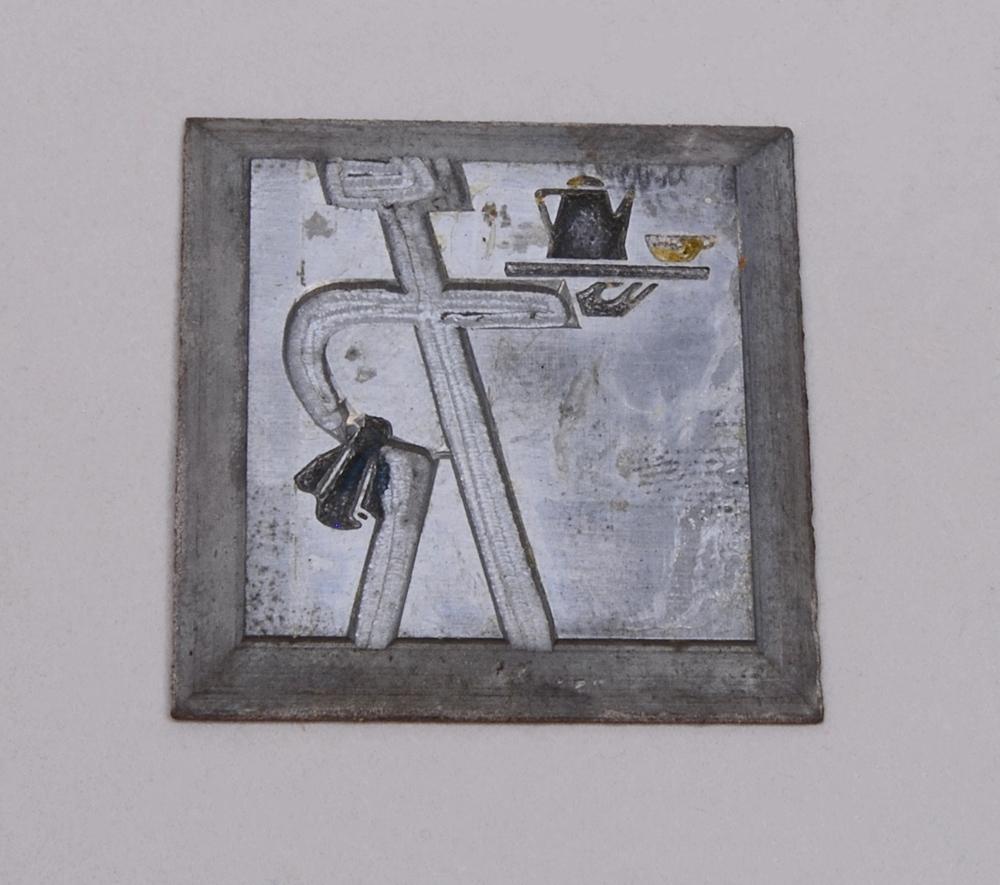 """Kvadratisk kliché av silverfärgad metall. På klichén finns Trafikrestaurangers logotyp med bokstäverna """"TR"""" sammanlänkade i form av """"TR-pojken"""". Den kallas TR-pojken eftersom det ser ut som en person som håller armen i en serveringsgest. I ena armen håller TR-pojken en bricka med en kanna och en kopp och över den andra armen, som vilar på höften, hänger en handduk. Logotypen är präglad."""