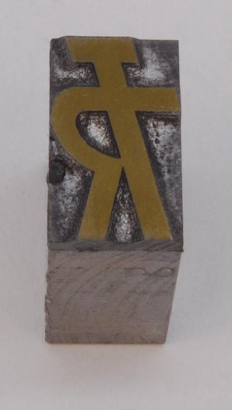 """Rektangulär kliché av silverfärgad metall, monterad på en silverfärgad metallkloss. På finns Trafikrestaurangers logotyp med bokstäverna """"TR"""" sammanlänkade i relief i form av """"TR-pojken"""". Den kallas TR-pojken eftersom det ser ut som en person som håller armen i en serveringsgest. Logotypen är grön."""