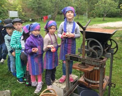 Elever i kø for å legge epler i eplepressa.. Foto/Photo