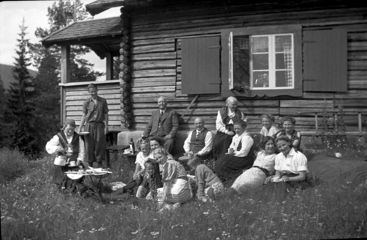 Hageselskap.Menn,kvinner og barn sitter på bakken foran tømmerhus.