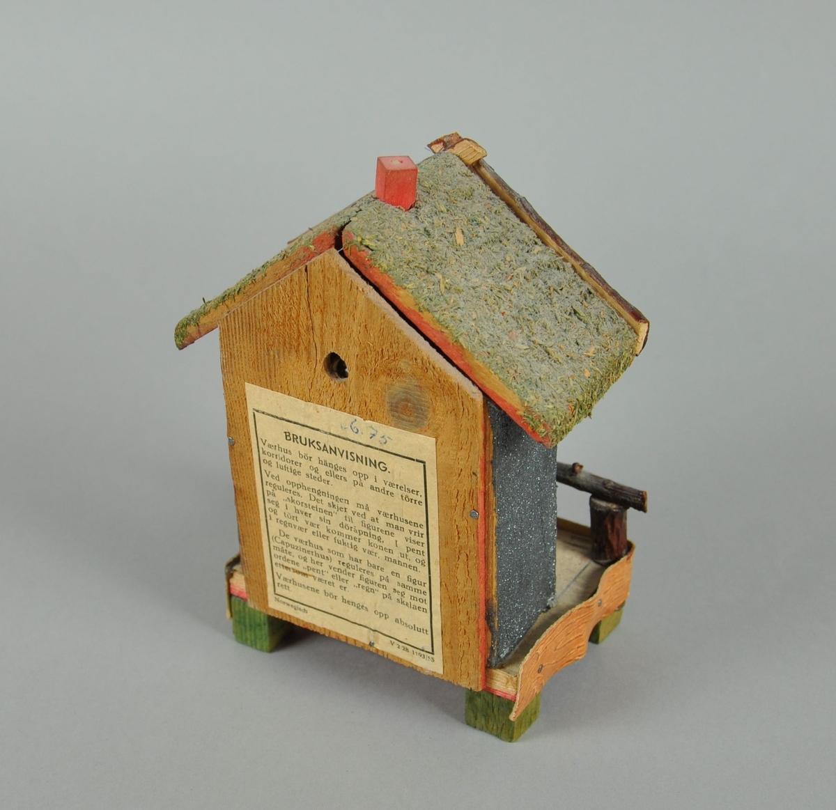 Værhus av tre, måler temperatur og lufttrykk. Forestiller et hus med veranda.  Mann og dame står på roterende stav og endrer posisjon utifra lufttrykk. Mellom dem er det gradstokk. På baksiden av huset er det bruksanvisning og hull for oppheng. Over gradstokk er det hode av hjort hvor geviret har falt av. Huset står på fire knotter. Veggene på huset har glitrende overflate.