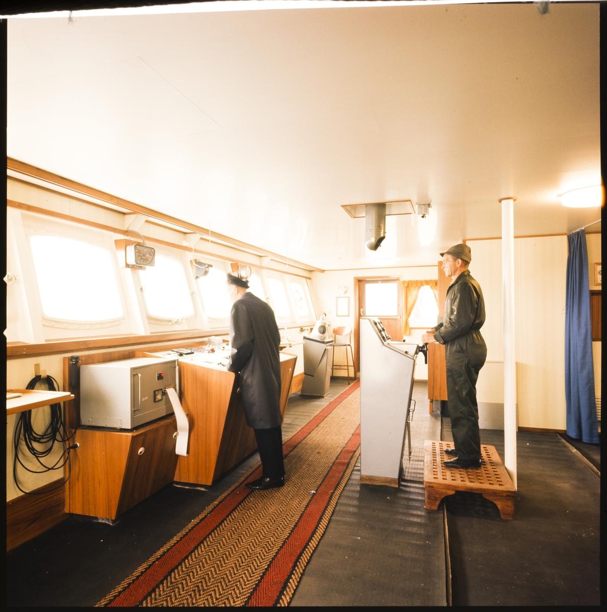 """To menn i arbeidsdress står i det nye styrehuset på bulkskipet """"Andwi""""."""