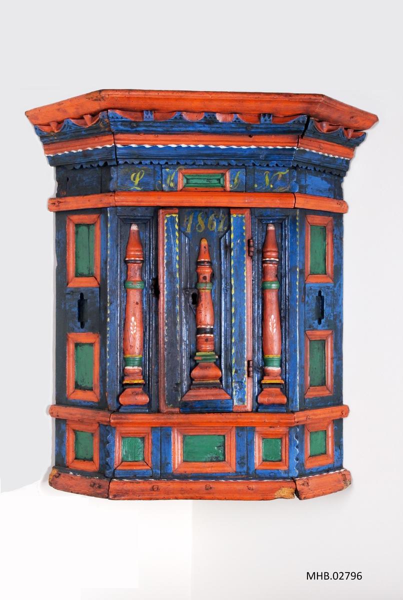 Blåmalt hjørneskap i renessansetil med profilert gesims. Tre balusterformet pilaster i front. Henglset dør.