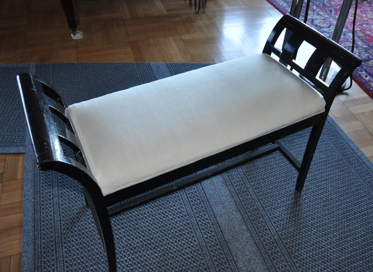 Pianokrakk av tre. Treverket er malt svart, setet er trukket med hvit tekstil. H-formet spross mellom beinene.