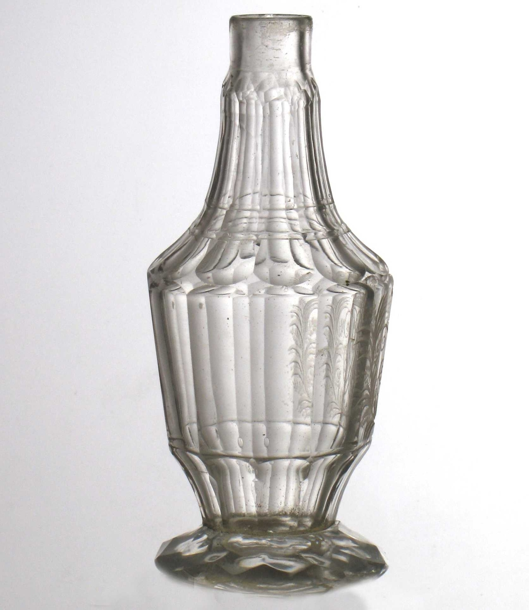 Glass, gravert kronet speilmonogram med en ranke på hver side. Fasettert fot,  mangekantet korpus og fasetterte skrå skuldre som smalner mot munningen.    Tilstand: propp mangler, limt fot.