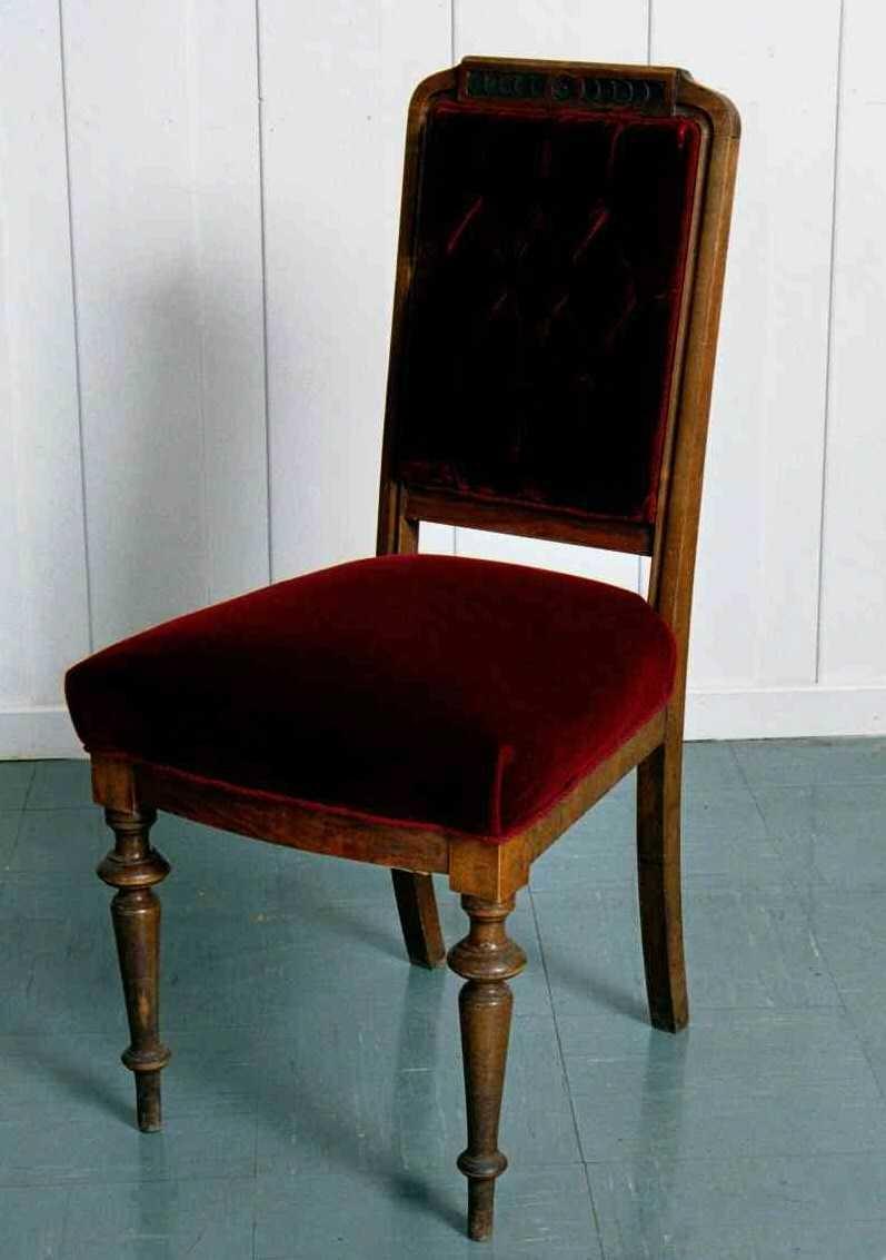"""10 stoler i nøttetre og rød plysj. Dreide forben, utskrådde glatte bakben, smal, svakt buet sarg. Høy rygg med dukatbord på ryggbrettet,  toppstykke, som er rett. Stoppet rygg med 9 """"knapper""""."""