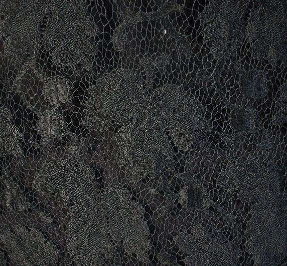 Svart klänning av genombruten maskinvävd trädd tyllspets. Helskuren med sydda kilar av georgette i sidorna och en mitt bak. Rund halsringning  med besparing av georgette. Lång isydd ärm av georgette, garnerad nedtill med en mönsterbård av stråpärlor och paljetter. Ärmens nedre kant förlängd med 12 cm vikt tyg i dekorativt syfte. Fästöglor i vardera axelsöm för fästning av underklänning. Mått: Hellängd 141cm, ärmlängd 47cm. Krage, rund formsydd, i georgette, knytband fram. På knytbandet mönsterbård av pärlor och paljetter. 5 st insnitt i nacken, kilfornad mönsterbård av pärlor och paljetter i kragens underkant. Mått: kragbredd 32 cm.