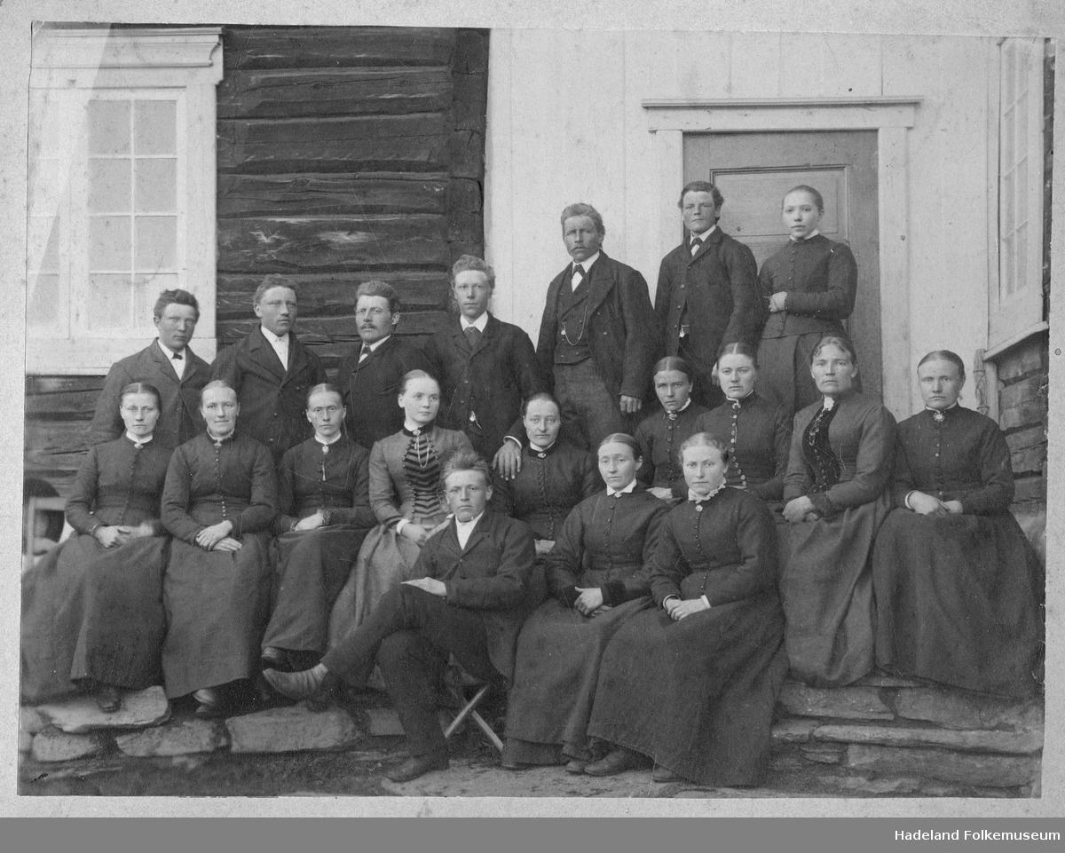 En gruppe på 12 kvinner og 7 menn samlet utenfor en tømmerbygning.