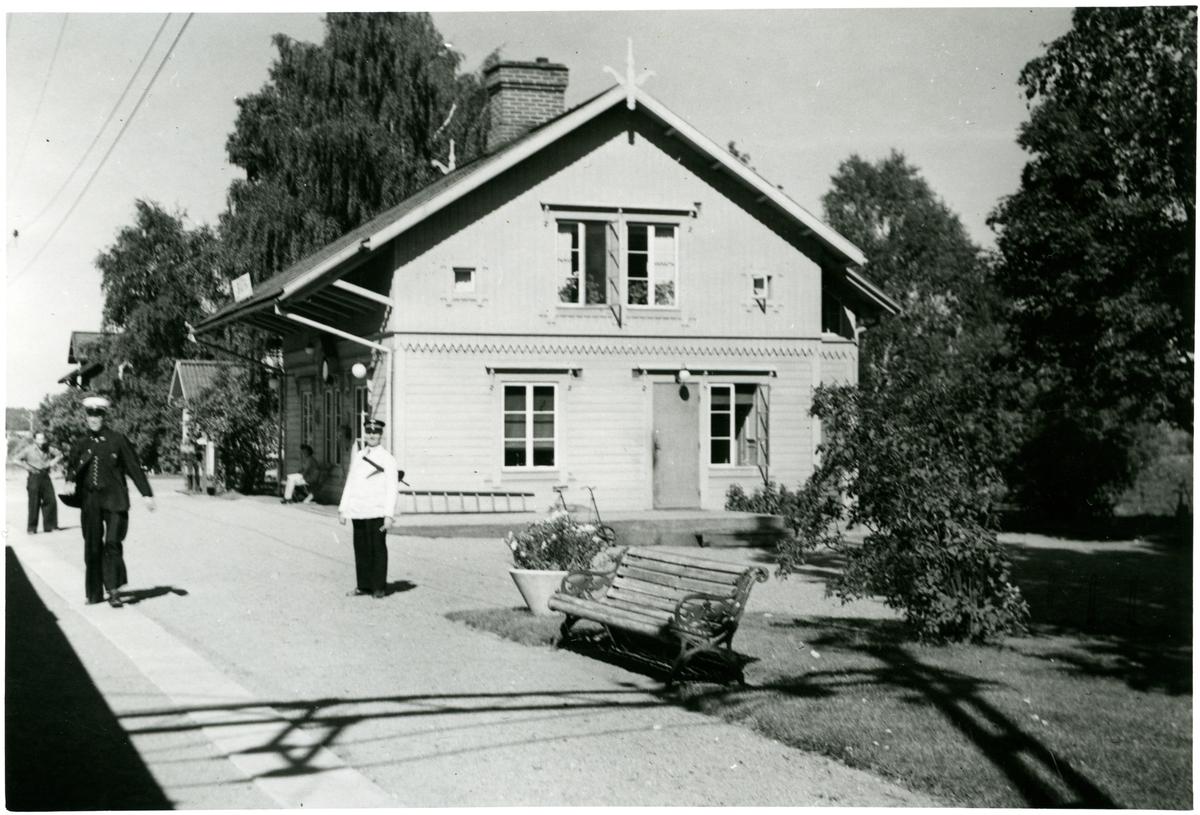 Skästra station med resande och personal på plattformen. Sommar.