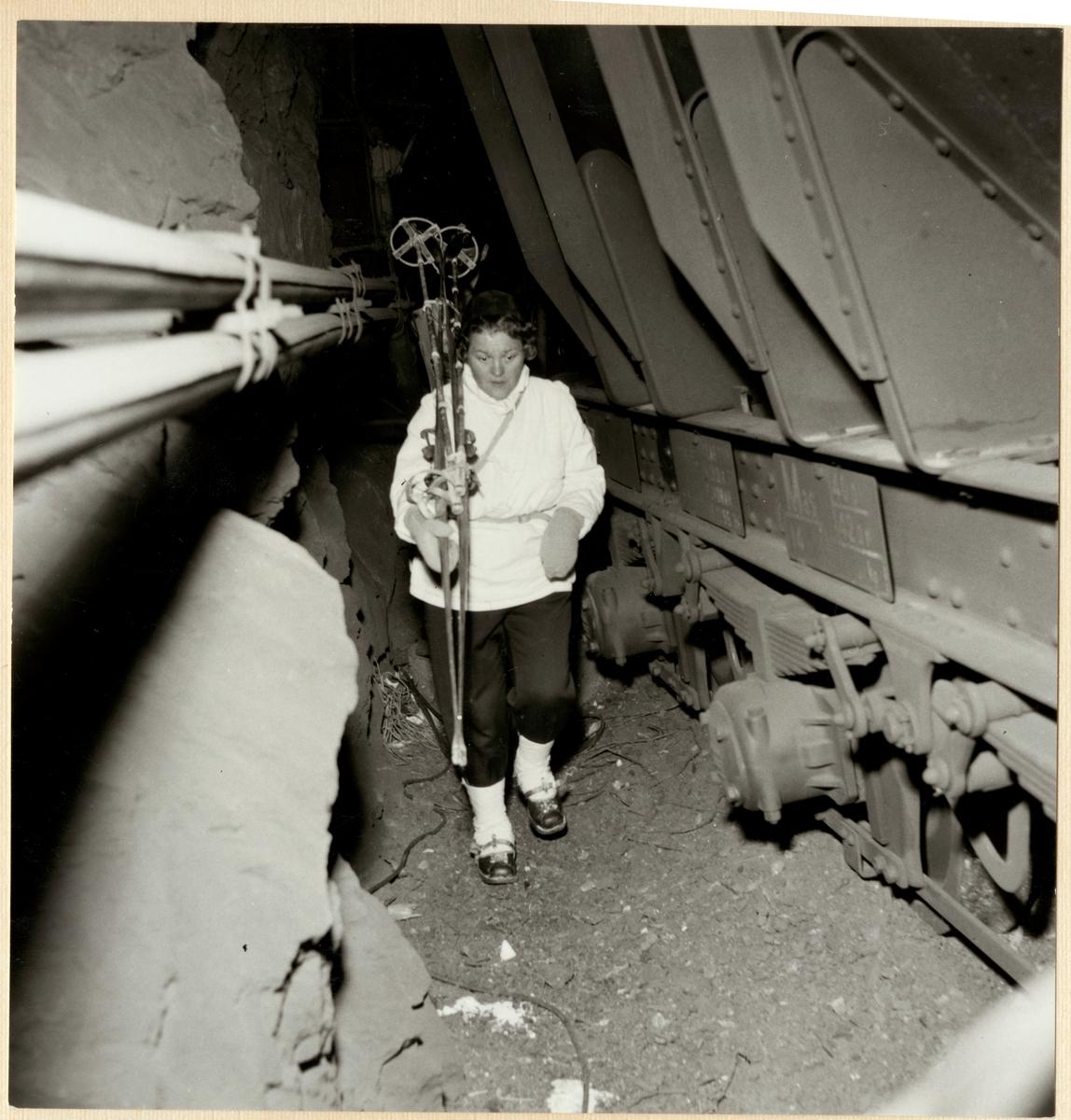 Statens Järnvägar, SJ, SJ Mas malmvagn, efter urspårning den 17/4 1956 på sträckan mellan Vassijaure och Hundalen. En kvinna går igenom tunneln där vagnarna spårat ur.