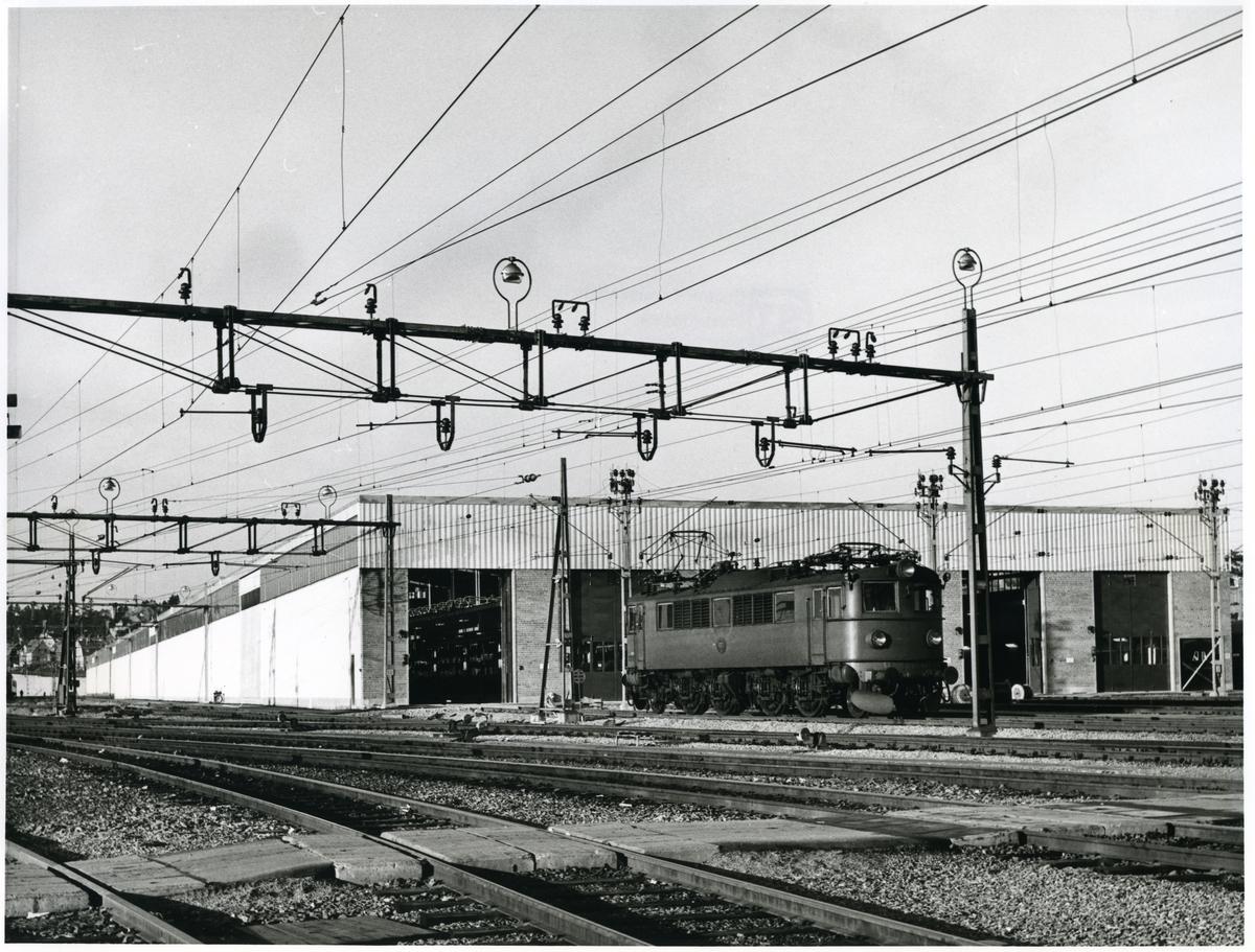 Statens järnvägars SJ F 627 lok som backar in genom portarna i vagnhallens sydöstra gavel för att hämta de färdiga tågsätten, på personbangården i Hagalund.
