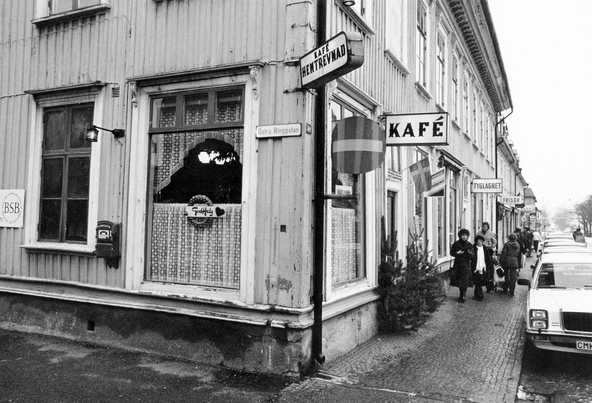 """Gatuvy från hörnet av Kungsgatan-Östra Ringatan som visar Café Hemtrevnads båda sidor. Över ingången en skylt """"Kafé"""". Trottoaren på Kungsgatan visar parkerade personbilar, människor samt skyltar med """"Tyglagret"""" och """"Frisör"""". Caféet lades ned vid årsskiftet 1980-81."""