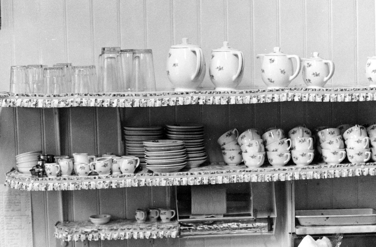 En hylla inifrån Café Hemtrevnad som visar urval av bland annat kaffeporslin, tekannor, fat och dricksglas. Caféet lades ned vid årsskiftet 1980-81