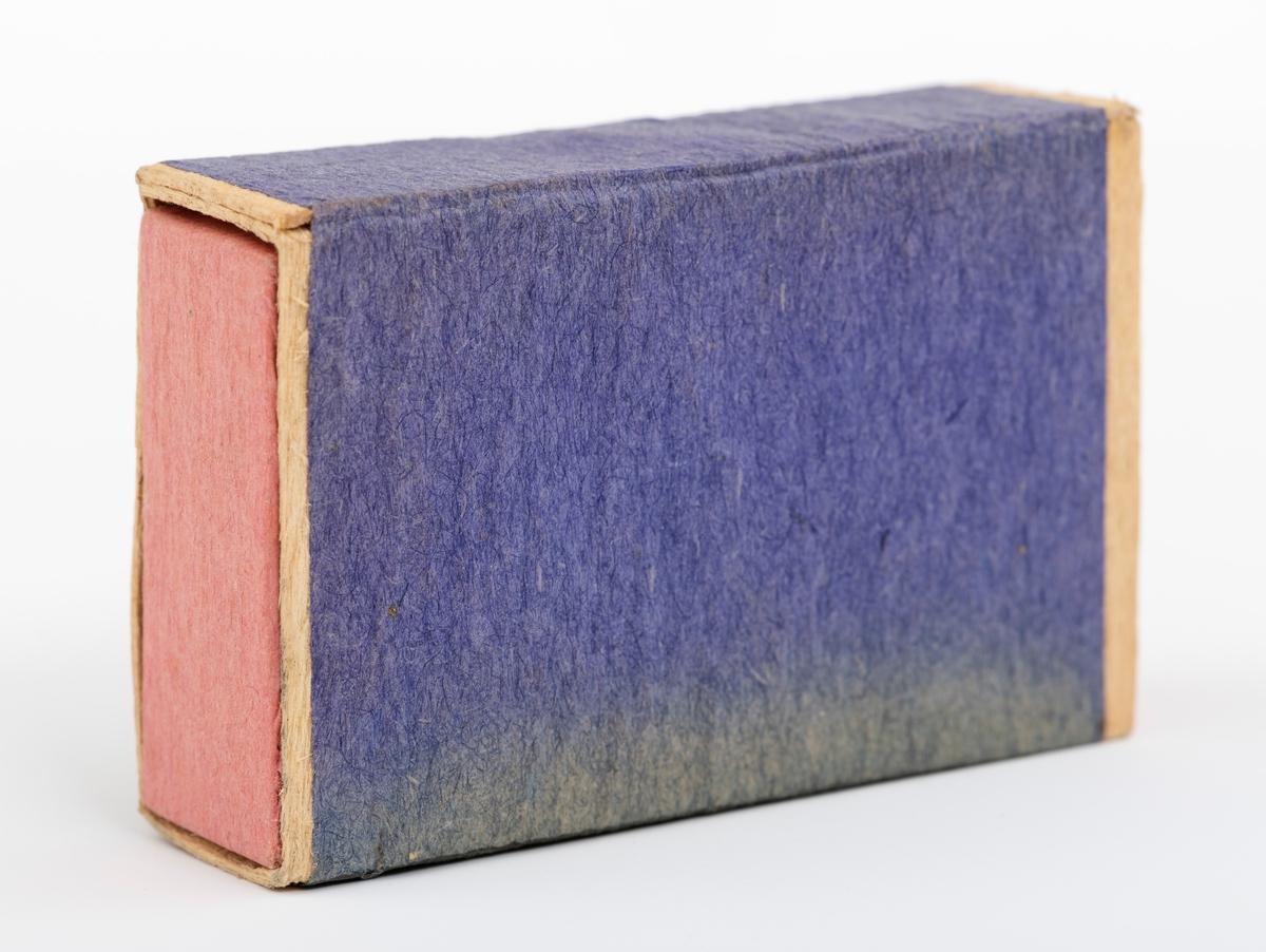 """Fyrstikkeske av gammel type. Esken består av to deler, hylster og skuff. Begge deler er laget av tynne trepalter som er sammenlimt med tynt papir. Skuffen har et rosafarget papir. Hylstrets dekorpapir har på framsida en etikett, baksiden er ensfarget blå. Den ene sideflata er blå, mens den andre er mer gråblå i fargen. Registrator oppfatter disse sideflatene som ripeflater for å få fyr på fyrstikkene. På etiketten er det avbildet en hest og to medaljer, henholdsvis fra Stockholm i 1866 og Paris i 1867. Esken er fylt opp med 46 ubrukte fyrstikker og 2 fyrstikker uten """"hode"""". Vi har ingen sikker datering for når esken er produsert."""