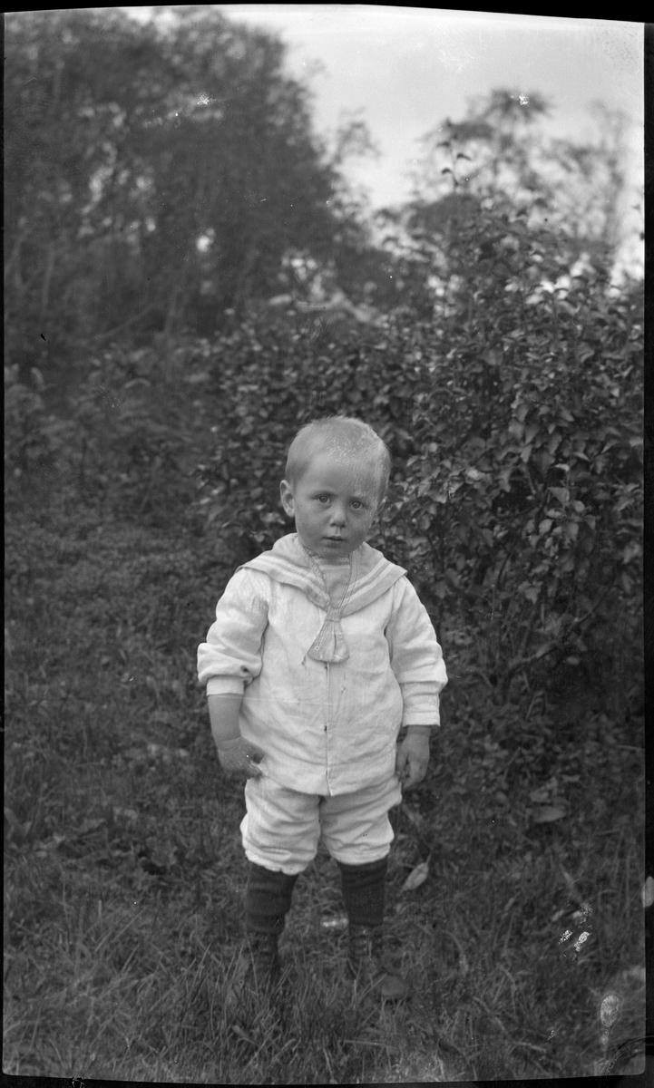 Portrett av liten gutt i matrosdress stående utendørs.