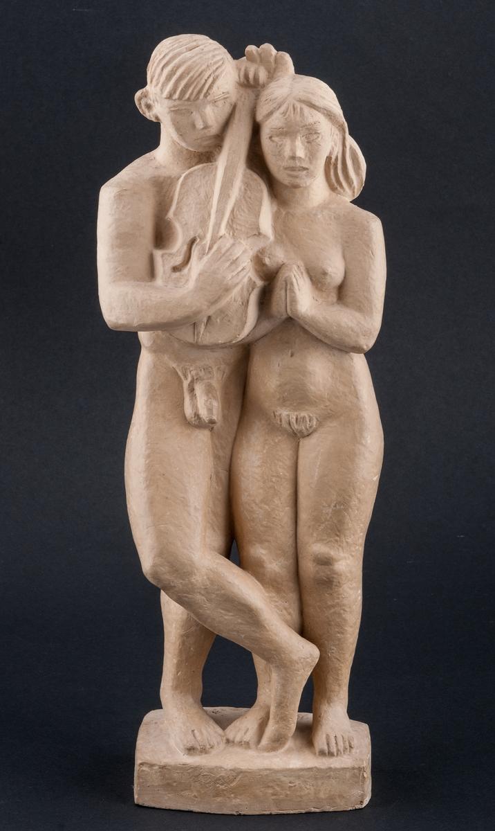 """Skulptur, gulfärgad gips. """"Flickan, pojken och fiolen"""". Stående par, han med korsade ben. Emellan sig har de en (alt)fiol, hållen av pojken. Rektangulär sockel signerad baktill på ovansidan: """"Bror Hjorth"""" samt på undersidan."""