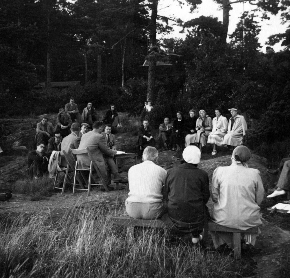 """Ett tjugotal personer på ett årsmöte vid strandkanten 1954. Anteckning på kortets baksida: """"Årsmöte 1954""""."""