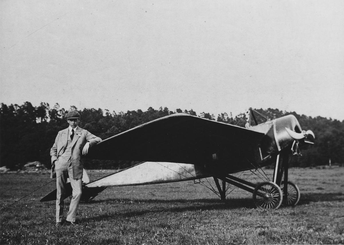 Porträtt av flygpionjären Enoch Thulin vid sitt flygplan. Thulin var den förste flygaren som besökte Alingsås. Detta skedde i samband med en av Alingsås Hantverksförening arrangerad fest i Nolhaga. Thulin gjorde uppstigningar från ett fält (senare gamla landbandybanan) bredvid festplatsen.